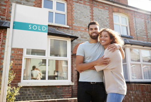 Happy couple standing outside a sold house
